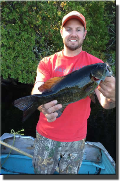 Image of Watershed Bear Outfitters' client with a bass - Gogama, Ontario